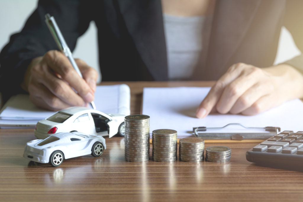 Car insurance and car service. Businesswoman with stack of coins and toy car, business and financial concept.